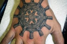 Detailed ship wheel tattoo on the hand