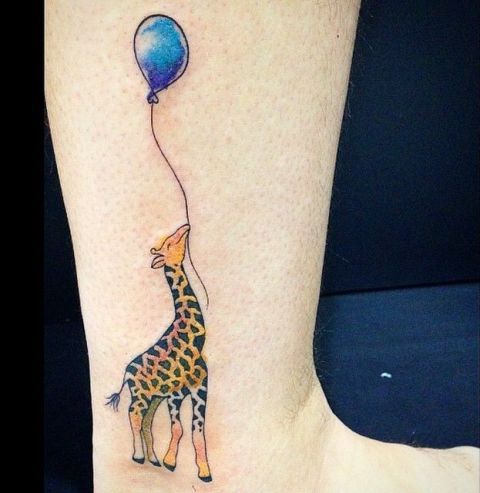 Giraffe and blue balloon tattoo on the leg
