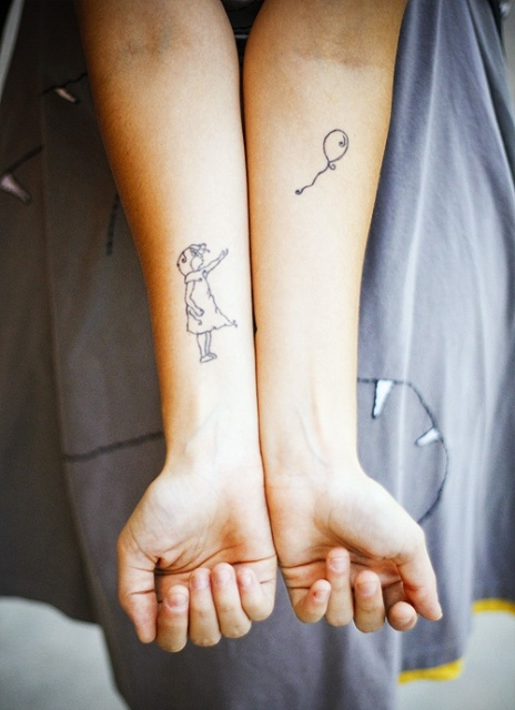 Girl with a balloon tattoo on the forearms