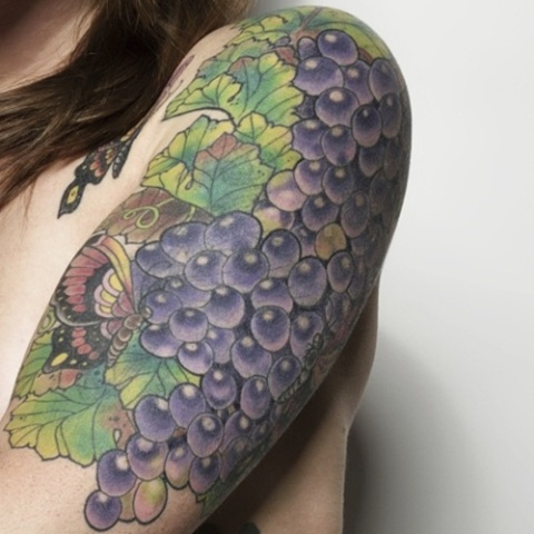 Grape with butterfly tattoo on the shoulder