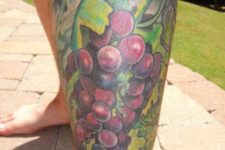 Green leaves and grape tattoo on the leg