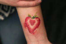 Half of a strawberry tattoo on the wrist
