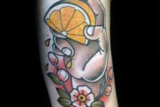 Hand holding a lemon tattoo