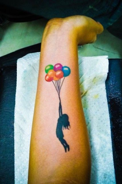 Lady with colorful balloons tattoo on the arm