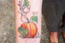 Orange pumpkin and green leaves tattoo