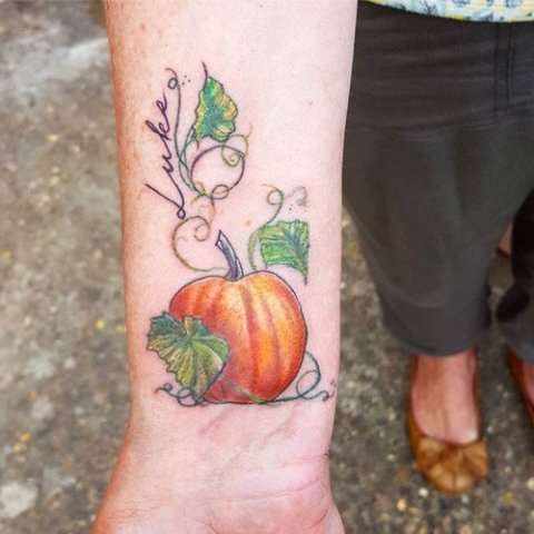 Orange pumpkin and green leaves tattoo