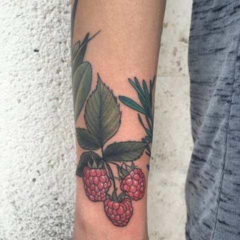 Pink raspberry and green leaves tattoo on the forearm