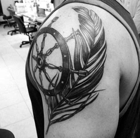 Ship wheel and feather tattoo on the shoulder