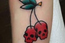 Skull shaped cherry tattoo on the hand