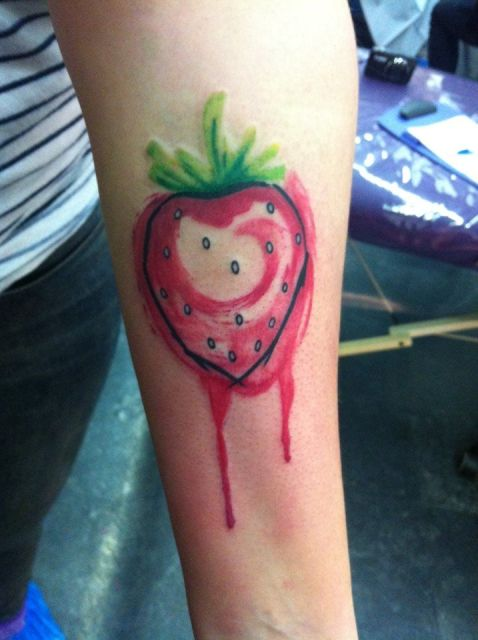 Watercolor strawberry tattoo on the forearm