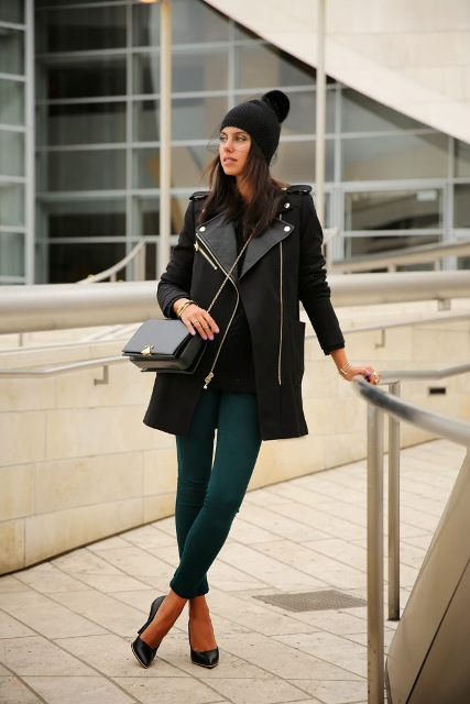 With black shirt, black leather bag, emerald pants, black heels and black coat