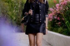 With black shirt, black leather mini skirt and bag