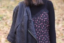 With black shirt, floral top, black pants and black leather jacket