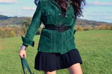 With black shirt, pleated skirt, high boots and green leather tote