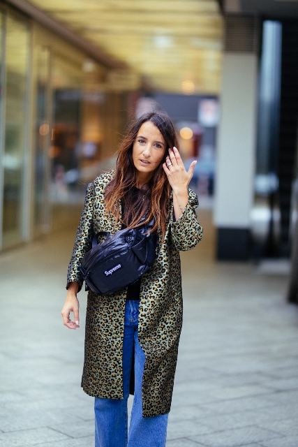 With black shirt, wide leg jeans and animal printed coat