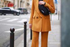 With black turtleneck, orange suit and black shoes