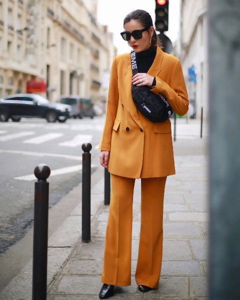 With black turtleneck, orange suit and black shoes