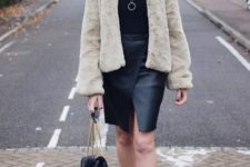 With black wrap skirt, black turtleneck, a mini bag and boots