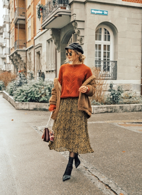 With orange sweater, cap, pleated skirt, sock boots and bag