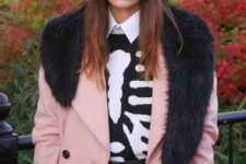 With pink coat with black fur, white shirt, printed sweater and skirt