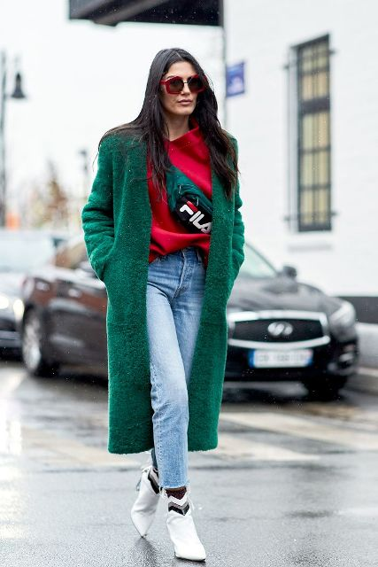 With red loose sweatshirt, crop jeans, green coat and white ankle boots