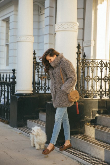 With skinny jeans, brown flats and brown small bag