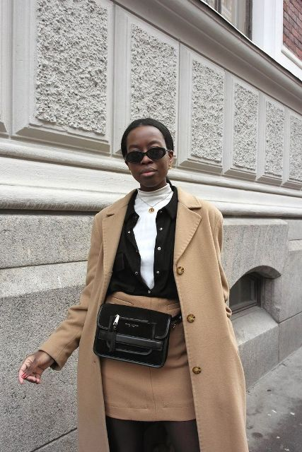 With white shirt, black shirt, camel skirt and coat