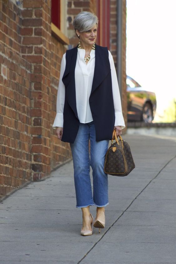 blue cropped jeans, nude shoes, a white shirt, a navy waistcoat and a classic bag plus jewelry
