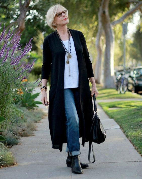 blue jeans, booties, a white top, a long black cardigan and layered necklaces plus a bag