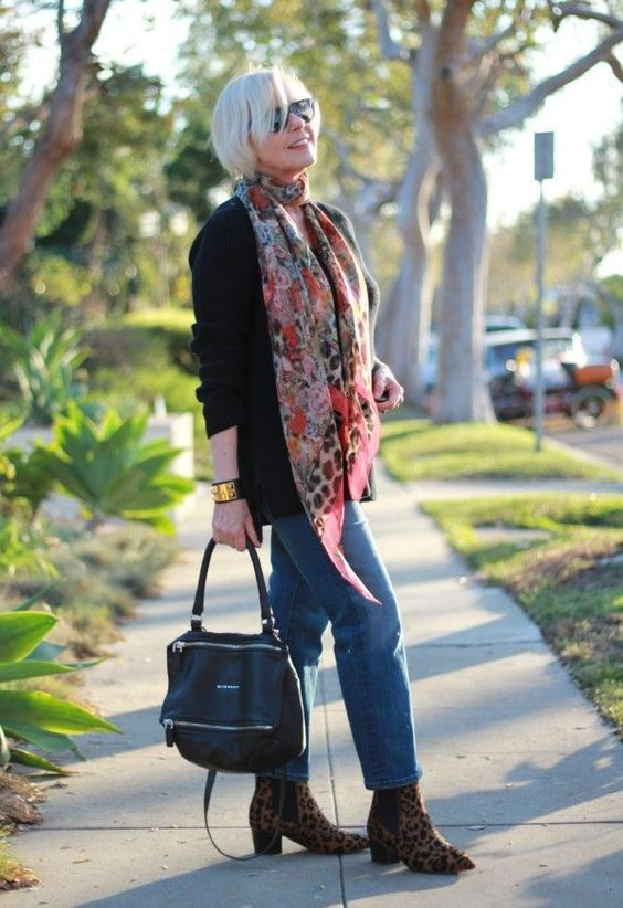 blue jeans, leopard booties a black sweater, a floral scarf and a black bag for a casual look