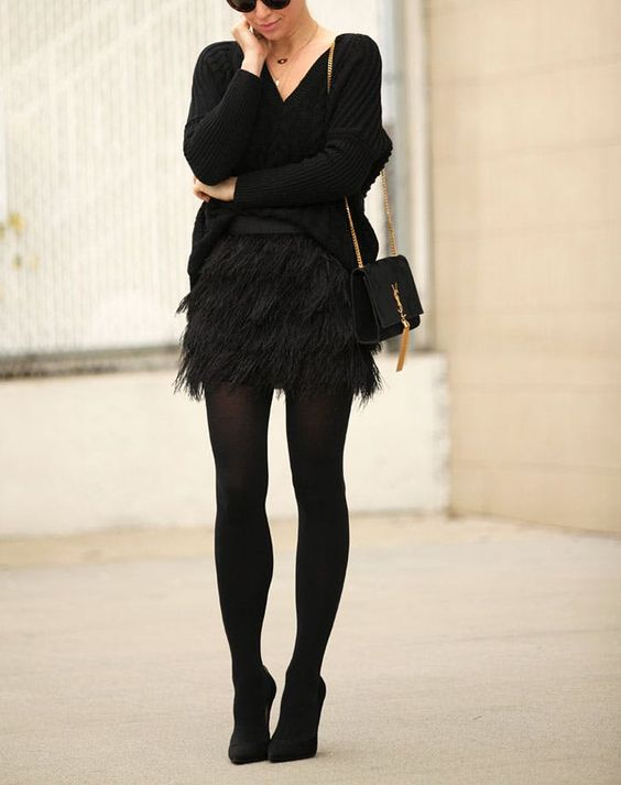 a black oversized sweater, a black feather mini, black tights, black pumps, a black clutch