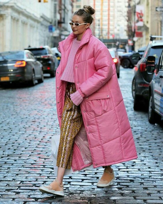 a cropped pink sweater, colorful striped cropped pants, camel sneakers and a midi pink puffed coat