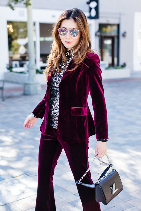 a plum-colored velvet pantsuit, a silver sequin top, a black bag for a cheery holiday look