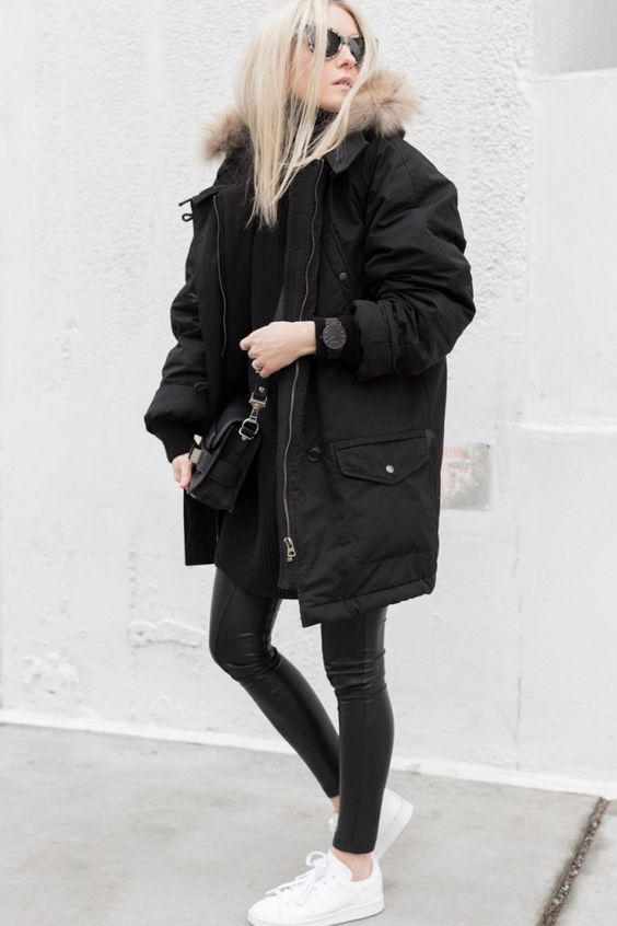 an outfit with a black sweater, black leather leggings, white sneakers and a black parka with faux fur