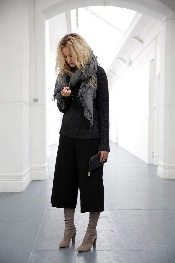 a black sweater, black culottes, grey boots, a grey scarf for a casual feel