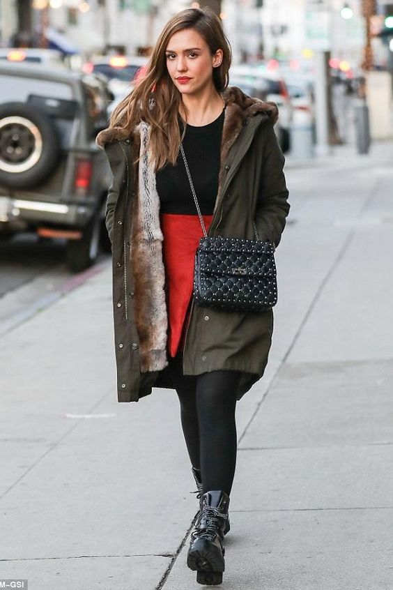 a red skirt, a black top, an olive green parka, black combat boots and a bag by Jessica Alba