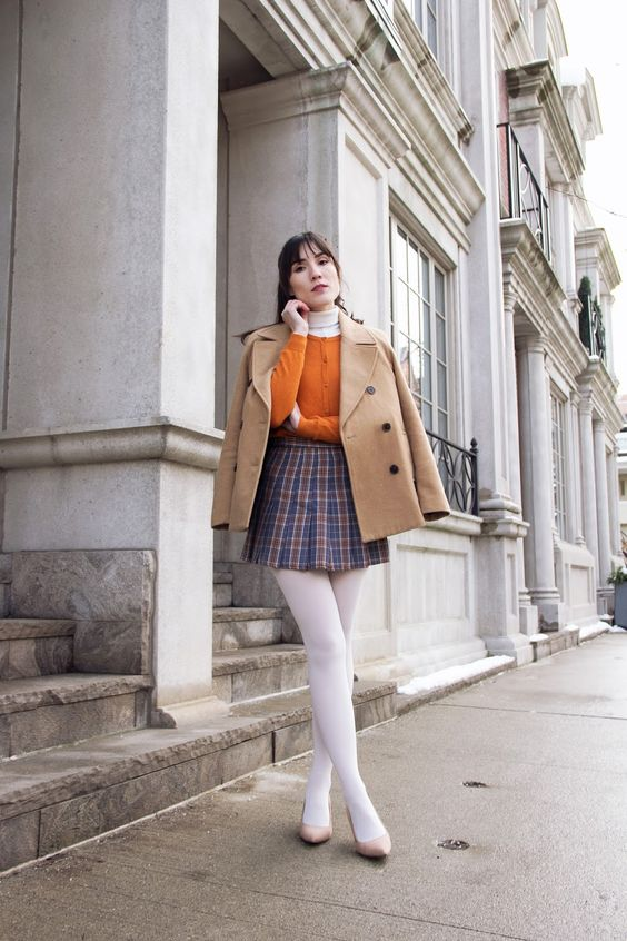 a vintage preppy look with a plaid mini, a white turtleneck, a mustard cardigan, white tights, a beige coat and nude shoes