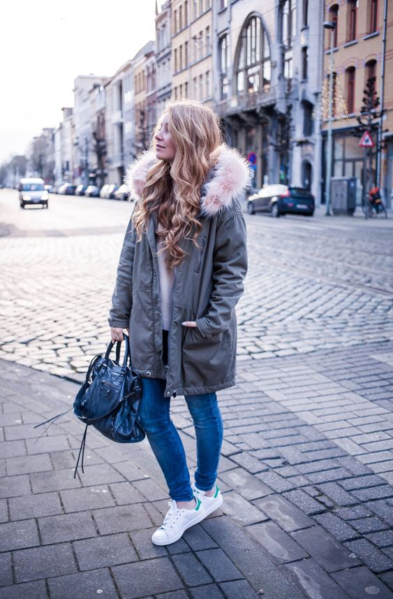 a white sweater, blue skinnies, white sneakers, a grey parka with faux fur and a bag