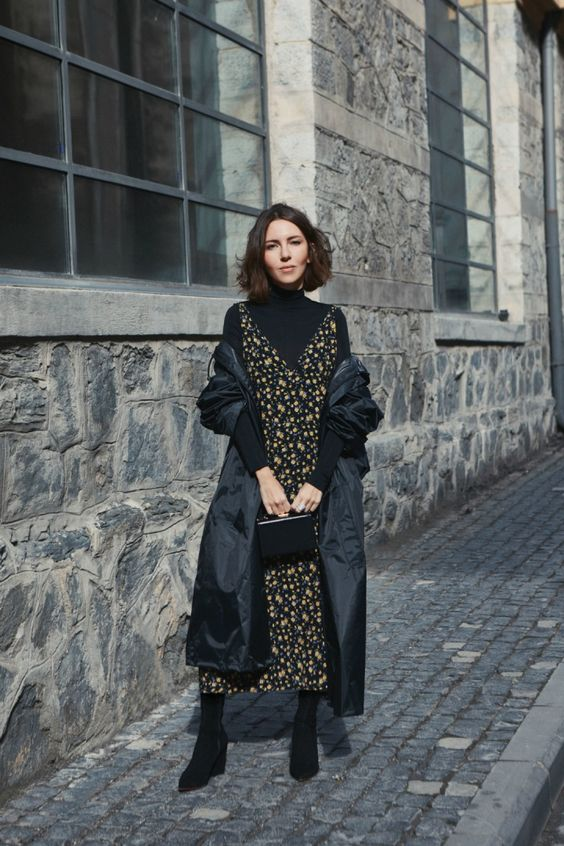 a black turtleneck, a moody floral midi dress over it, sock boots, a small bag and a puff midi coat