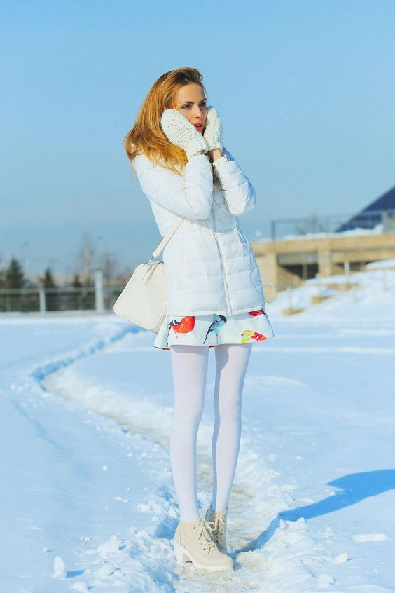 a girlish look with a bright printed mini dress, creamy boots, white tights, a white puffed coat, creamy mittens and a bag