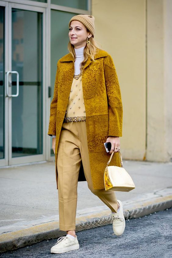 a monochromatic outfit with pale yellow pants, an embellished top, a white turtleneck, a mustard fur coat and neutral sneakers