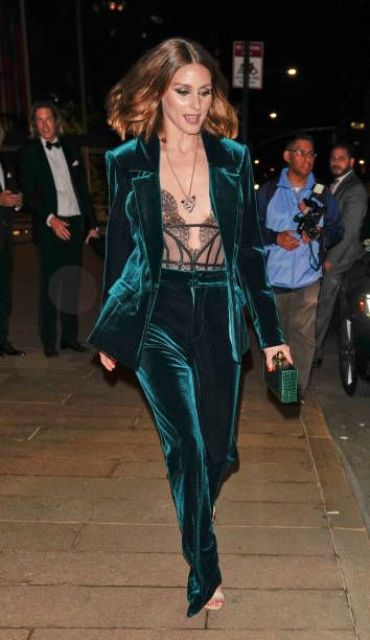 an emerald velvet pantsuit with a lace corset and a green clutch for an ultimate holiday look
