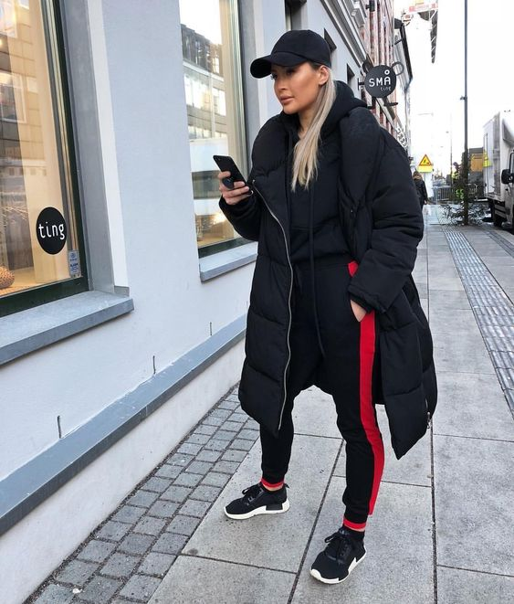 a black and red tracksuit, a midi puff coat, black trainers and a cap for a fully sport look