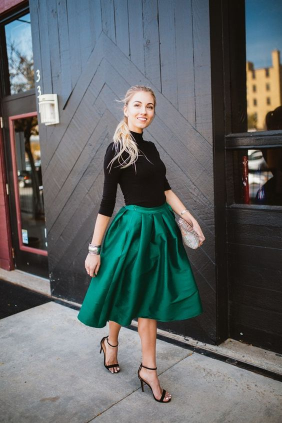 a black turtleneck, an emerald A-line midi skirt, black heels and a shiny clutch create a playful look