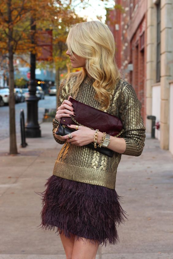 a gold cable knit sweater and a maroon feather skirt plus a matching clutch to sparkle