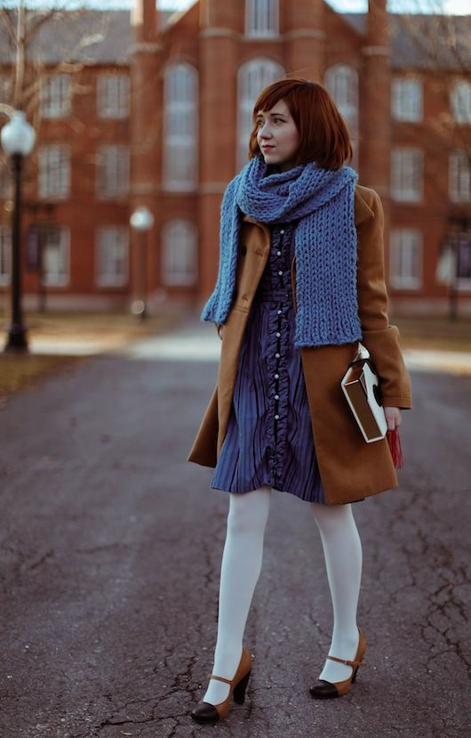 a preppy vintage-inspired winter look with a blue dress and scarf, white tights, camel shoes and a coat