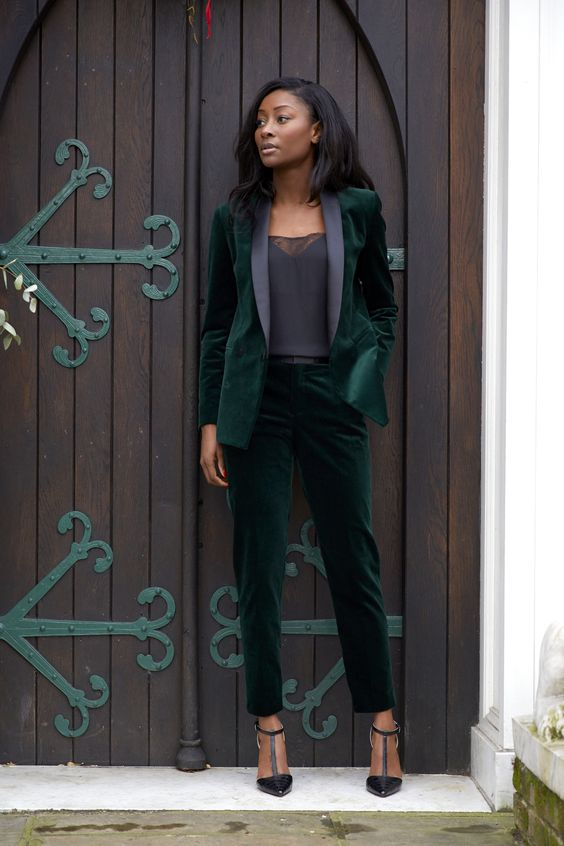 an emerald velvet pantsuit with black lapels, a black top with lace and black T strap heels for a party