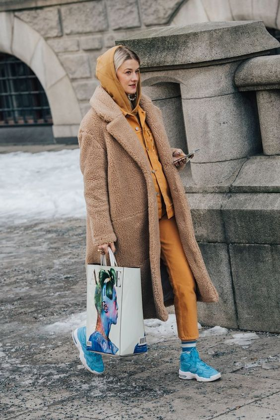 a yellow hoodie, cropped jeans, bold blue sneakers and a camel faux fur coat