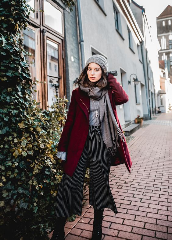 striped culottes, black boots, a grey top, a scarf, a beanie and a burgundy coat for a festive look