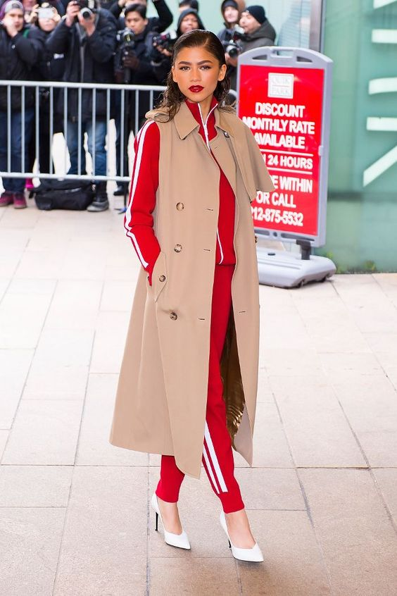 a red tracksuit, a beige duster coat and white heels for a style statement